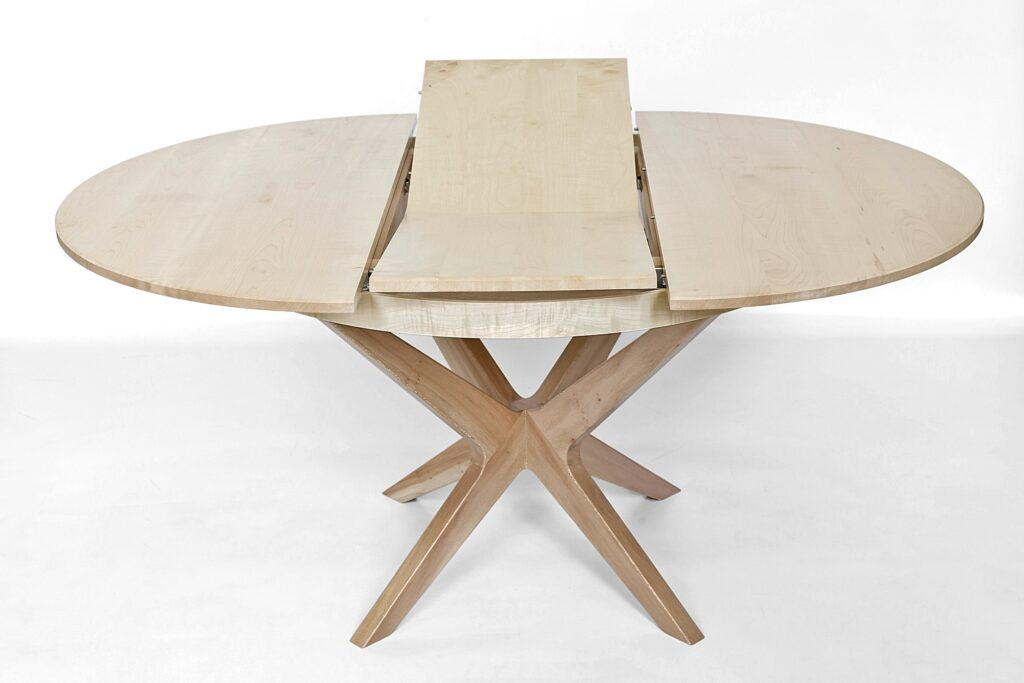 Extending dining table showing butterfly leaf extension