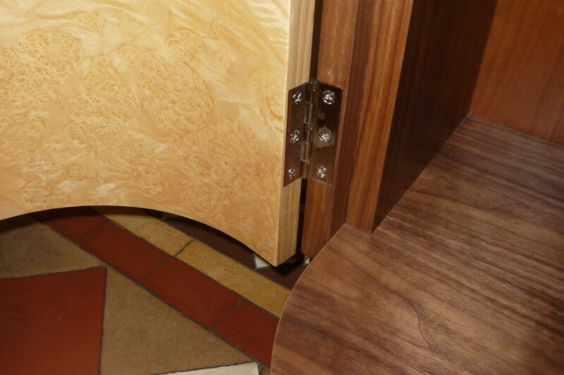 Detail at base of curved door on hall cabinet