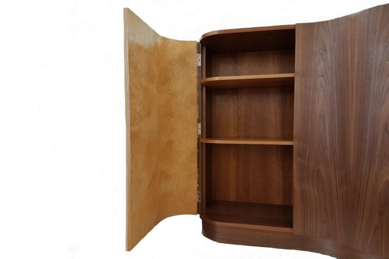 Contemporary hall cabinet with curved door open displaying cherry shelves inside