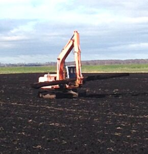 Collecting a Bog Oak Log from Fields, using a tracked machine