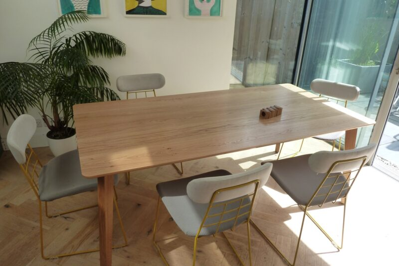 Large oak dining table with chairs set around