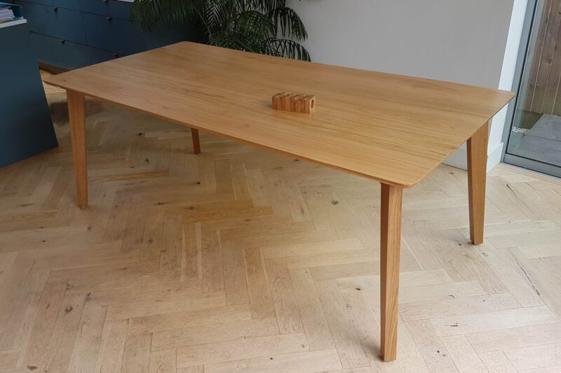 Mid-century modern style oak dining table with splayed and tapered legs