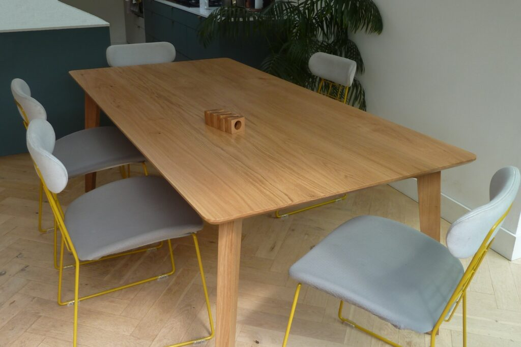 Scandinavian style oak dining table with chairs around
